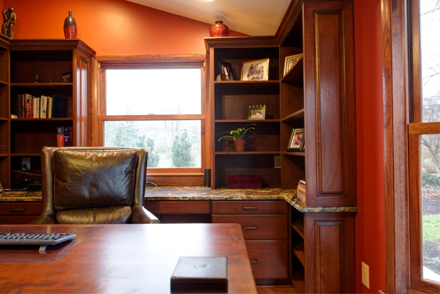 The bookshelves and desk were hand-built using two kinds of cherry wood. The large bay windows make the living space brighter and more inviting.