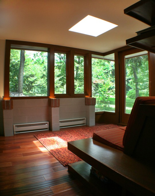 Sun room interior with seamless corner window and light well.