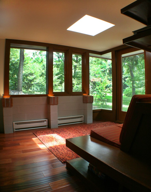 Sun room interior with seamless corner window and light well.