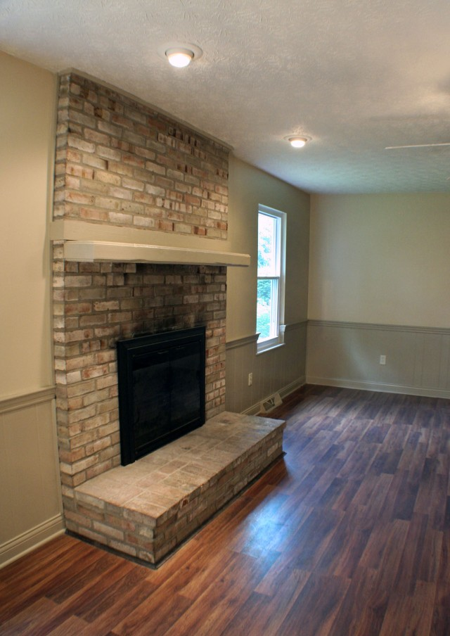 Cozy living room with large center fireplace , new flooring, and trim details.