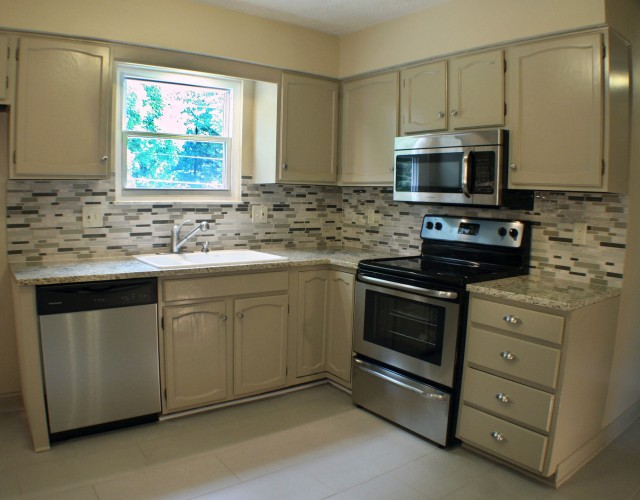 The cabinets were refinished and glass wall tile was added to this charming kitchen.